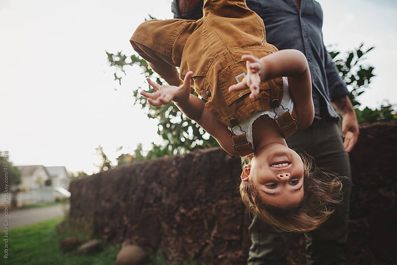 Young, stylish dad holds cute happy toddler girl upside down - outside by Rob and Julia Campbell for Stocksy United