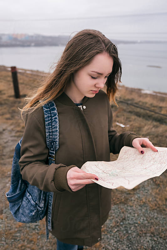 Teenage traveler looking at map by Danil Nevsky for Stocksy United