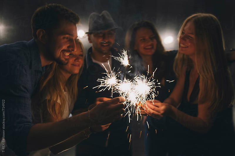 Friends at night club with sparklers by Danil Nevsky for Stocksy United