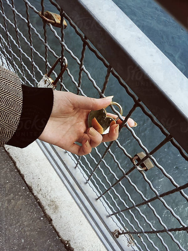 Young woman holding heart padlock on bridge of love by Hamza Kulenović for Stocksy United