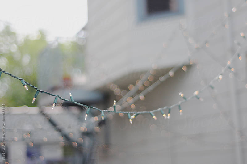 Twinkle lights hang in a city alley by Chelsea Victoria for Stocksy United