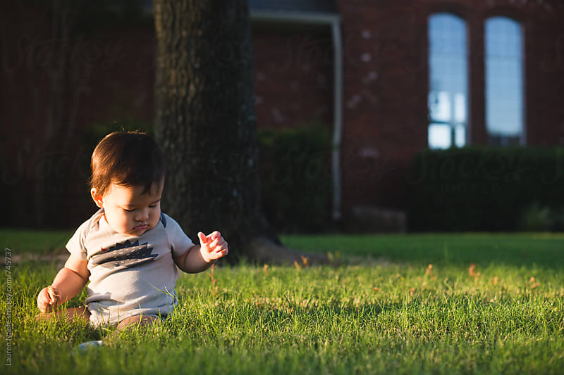 Baby playing by himself on the grass by Lauren Naefe for Stocksy United