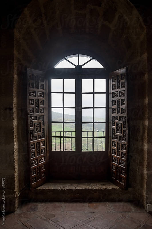 An arched window looking out to scenic country. by Mike Marlowe for Stocksy United