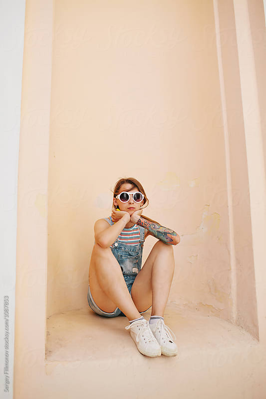 Trendy tattooed model sitting in niche  by Sergey Filimonov for Stocksy United