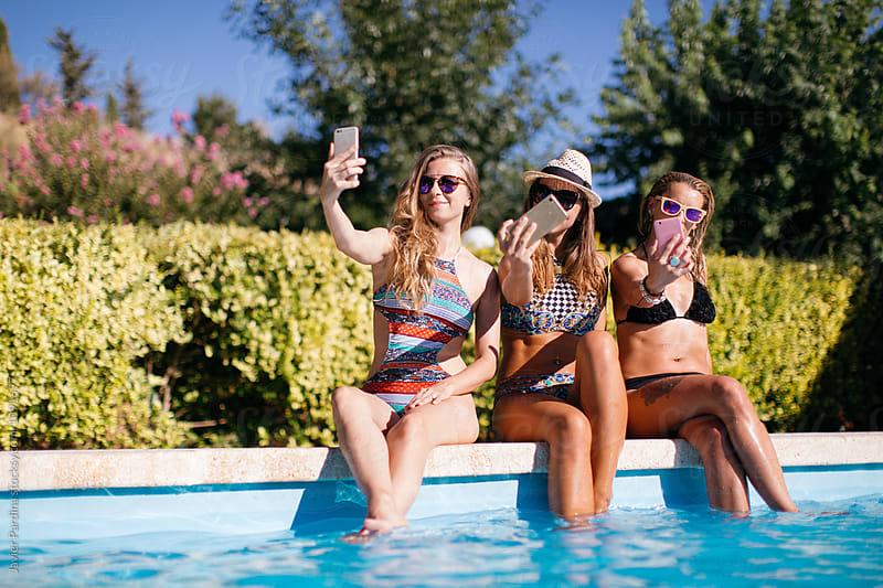 women enjoy in the pool by Javier Pardina for Stocksy United