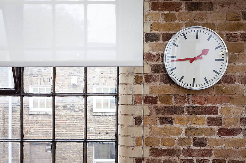 Wall clock and brick work by James Tarry for Stocksy United