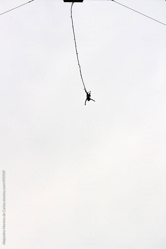 Silhouette of a person bungee jumping from a platform with white background by Alejandro Moreno de Carlos for Stocksy United