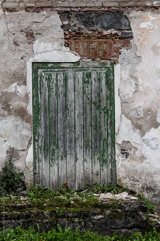 Decaying door of a decaying house by Melanie Kintz for Stocksy United