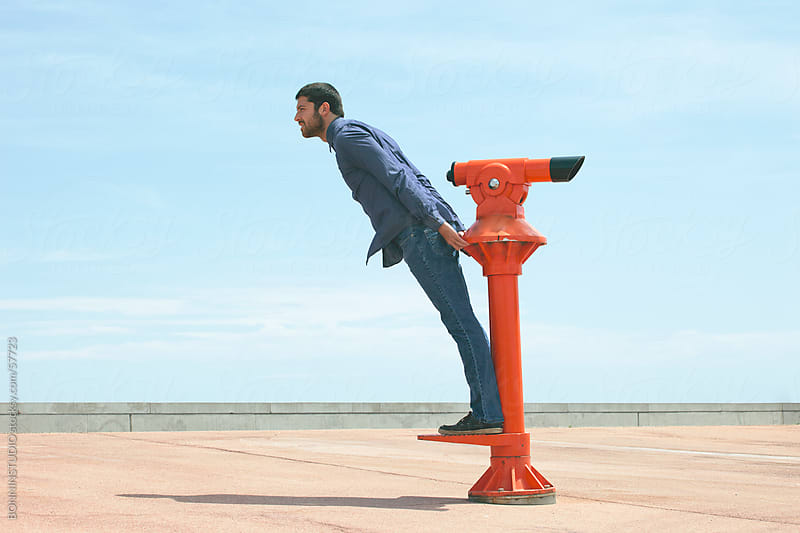 Young man balancing on red telescope in front of blue sky. by BONNINSTUDIO for Stocksy United