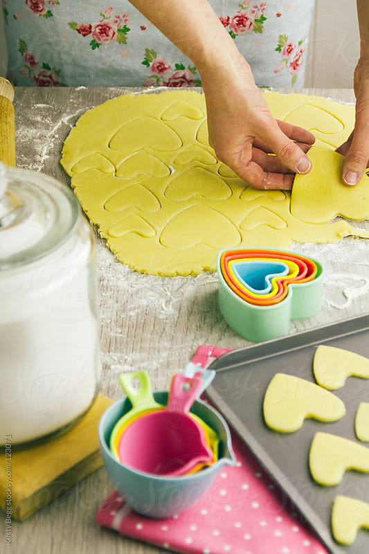 Woman cutting out heart shaped cookies by Kirsty Begg for Stocksy United