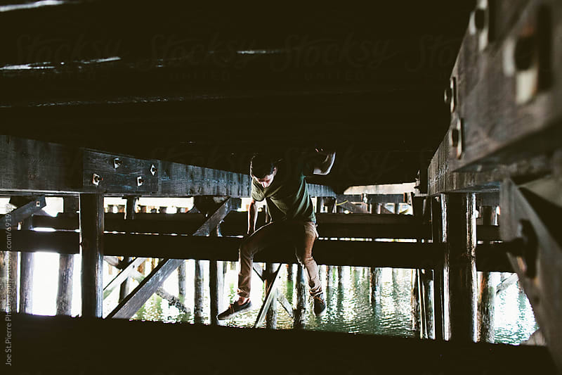 Young man sitting under bridge by Joe St.Pierre Photography for Stocksy United
