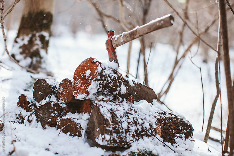 Axe stack in stacked tree trunks in a snowy forest.  by BONNINSTUDIO for Stocksy United