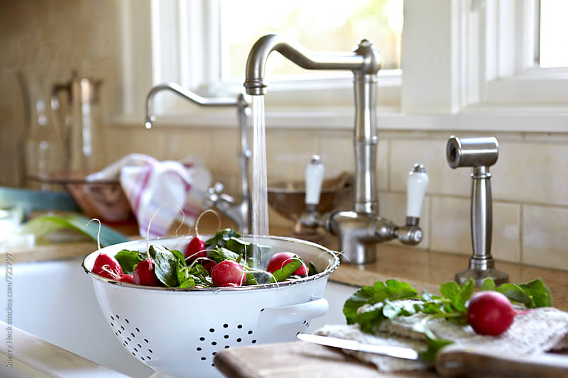 Radishes being washed in colendar in sink by Sherry Heck for Stocksy United