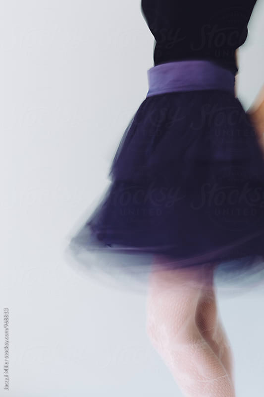Feminine movement shot of woman wearing purple tulle skirt by Jacqui Miller for Stocksy United