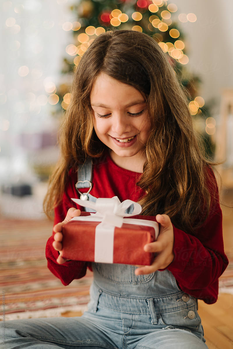 excited girl opening christmas presents by dejan ristovski for stocksy united