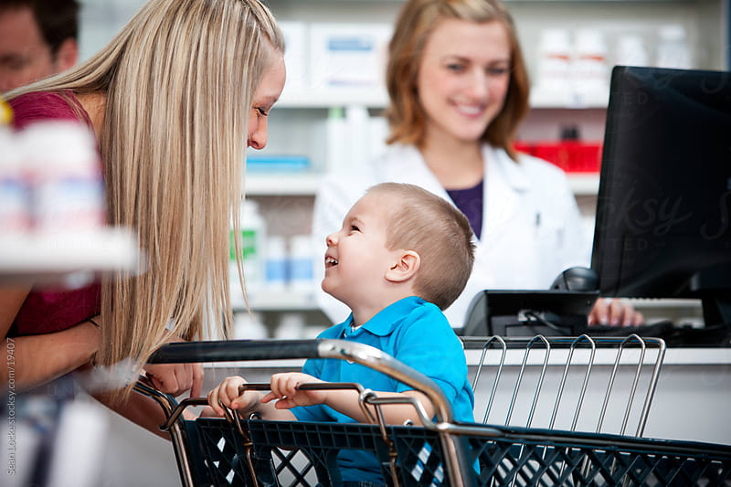 Pharmacy: Mother Laughing with Son in Shopping Cart by Sean Locke for Stocksy United