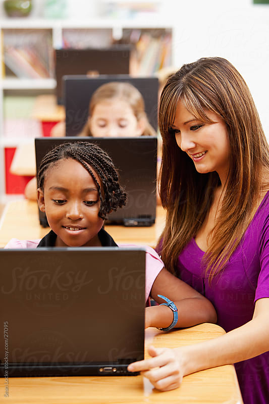 Classroom: Teacher Helps Student with Laptop by Sean Locke for Stocksy United