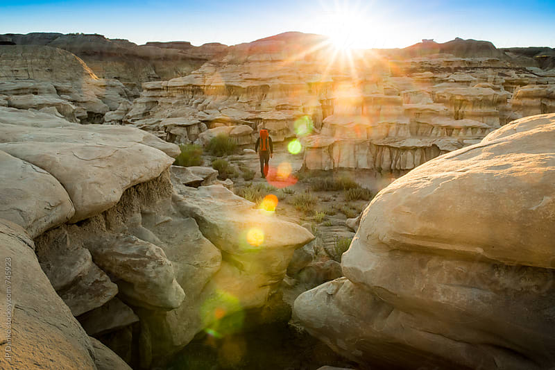 Backpacker Hiking in Hoodoo Wash in Bisti Badlands Wilderness Area New Mexico at Sunrise by JP Danko for Stocksy United