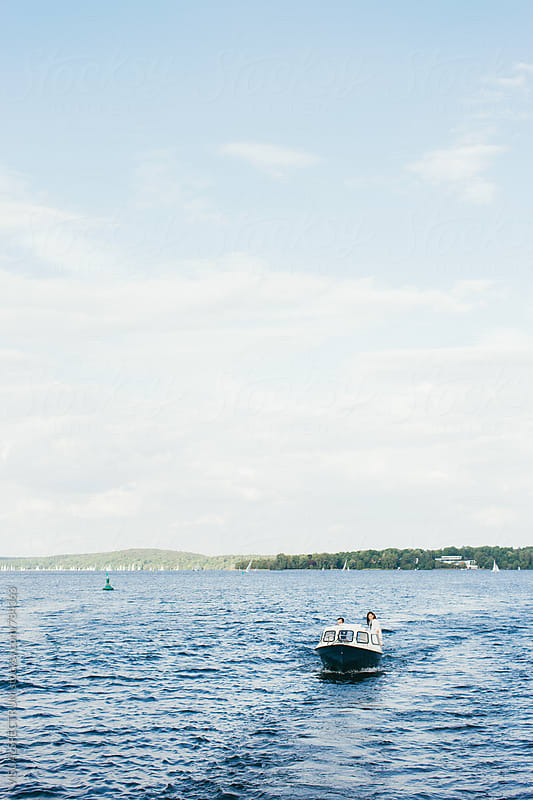 Caucasian Couple on Small Motorboat on Big Lake by VISUALSPECTRUM for Stocksy United