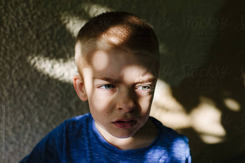 Portrait of boy in dappled light. by Julia Forsman for Stocksy United