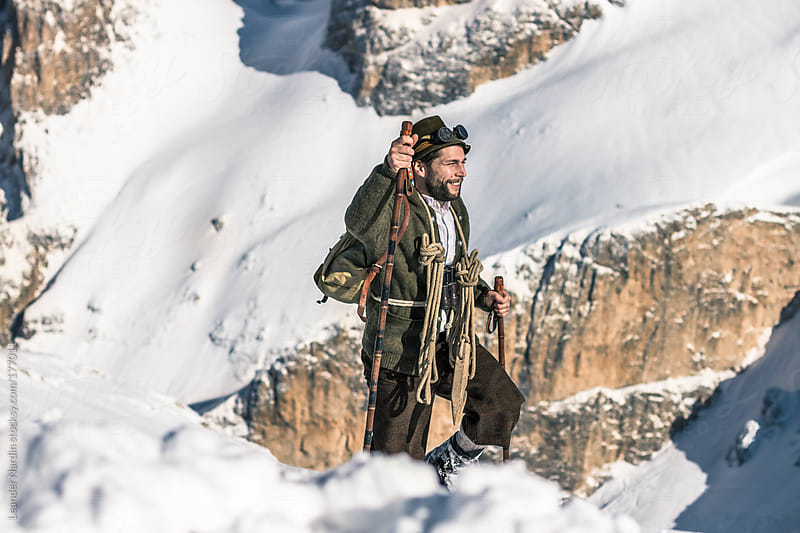 man in old, nostalgic mountaineering outfit hiking up a snowcoverd mountain by Leander Nardin for Stocksy United