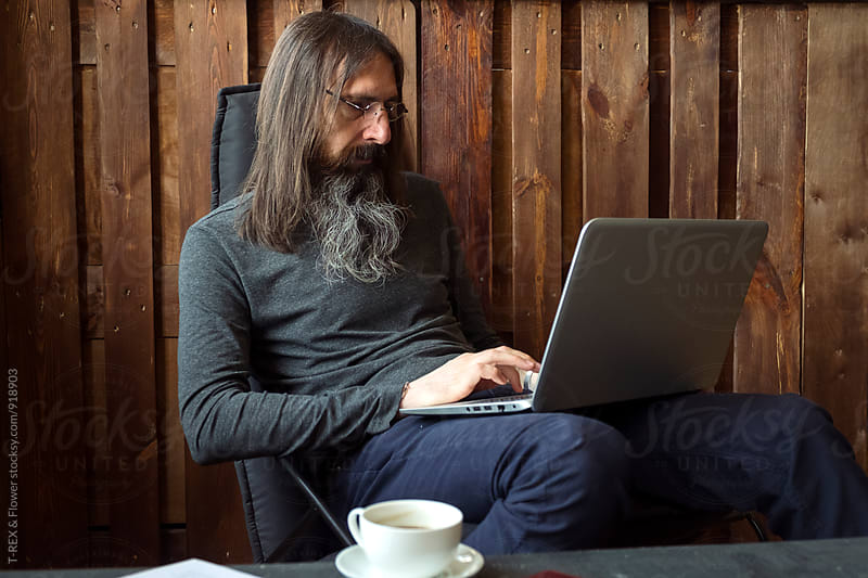 Aged long haired man sitting on chair while using laptop by T-REX & Flower for Stocksy United