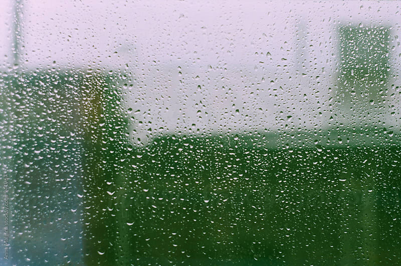 A film photo of a window with a rain drops on it by Anna Malgina for Stocksy United