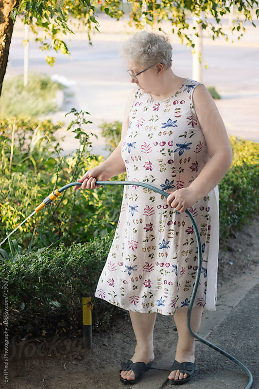 Adult female model washing flowers  by Branislava Živić for Stocksy United