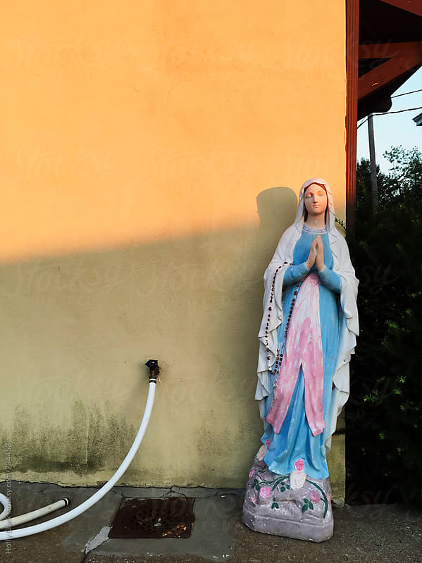 Virgin Mary statue against a dirty wall  by Holly Clark for Stocksy United