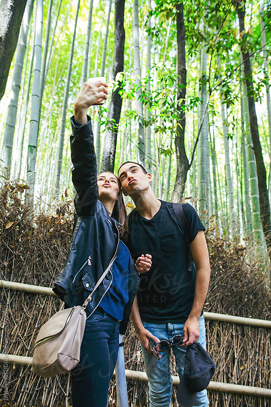 Tourist friends taking a selfie in bamboo forest. by BONNINSTUDIO for Stocksy United