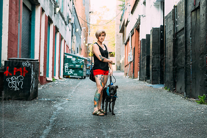 Young Blonde Tattooed Woman Standing Next To Pet Pit Bull On Leash In City Alley by Luke Mattson for Stocksy United