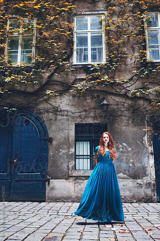 Dreamy portrait of a young woman in a long blue dress by Jovana Rikalo for Stocksy United