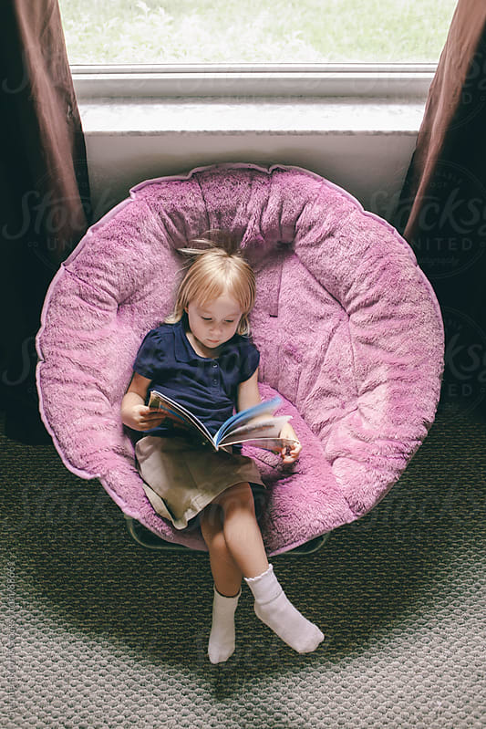 Little girl reading book by window by Stephen Morris for Stocksy United