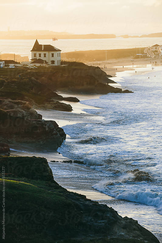 Beatiful and natural scene of the waves on the shore with houses in the background by Alejandro Moreno de Carlos for Stocksy United