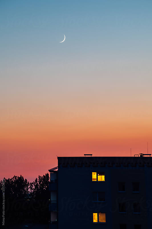New moon over silhouetted building with lights by Mima Foto for Stocksy United