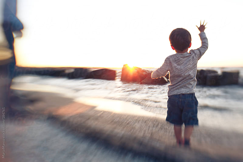 child looks out on water at sunset by Maria Manco for Stocksy United