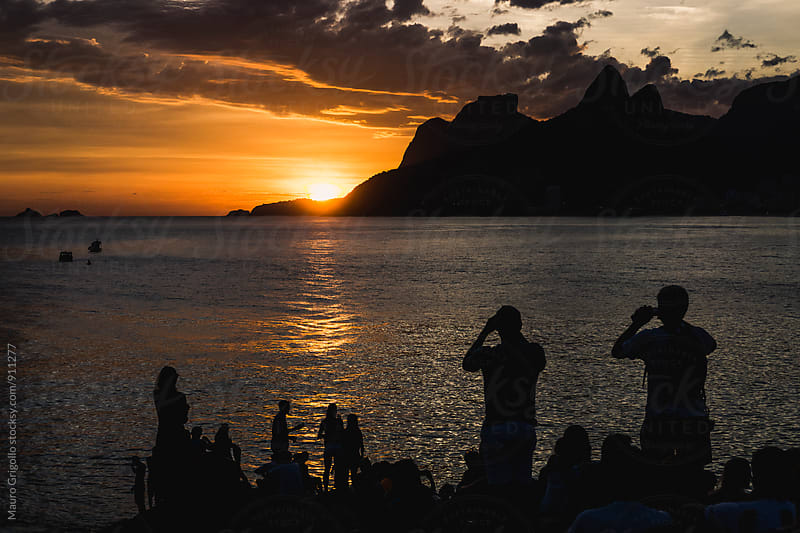 Silhouette of people looking at sunset by Mauro Grigollo for Stocksy United