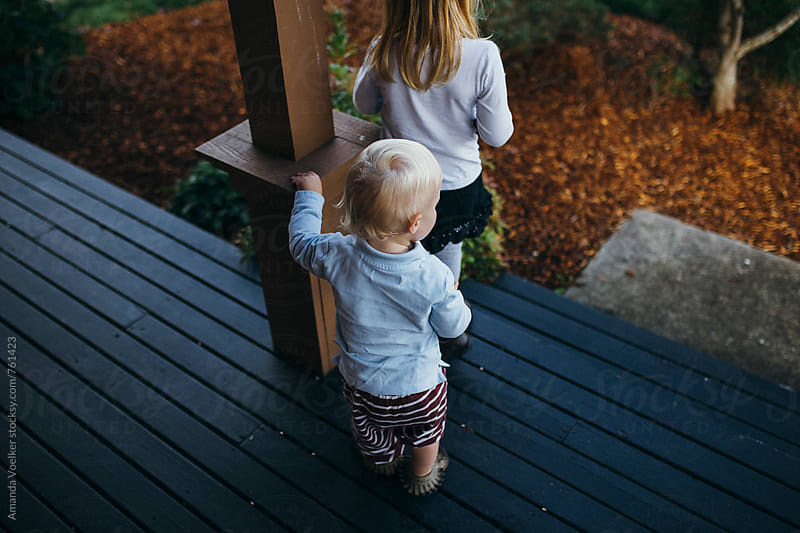 Back view of two young children walking off the porch by Amanda Voelker for Stocksy United