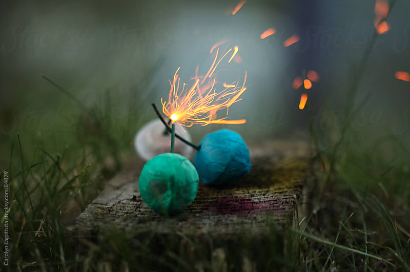 Colorful smoke bombs with sparks flying by Carolyn Lagattuta for Stocksy United