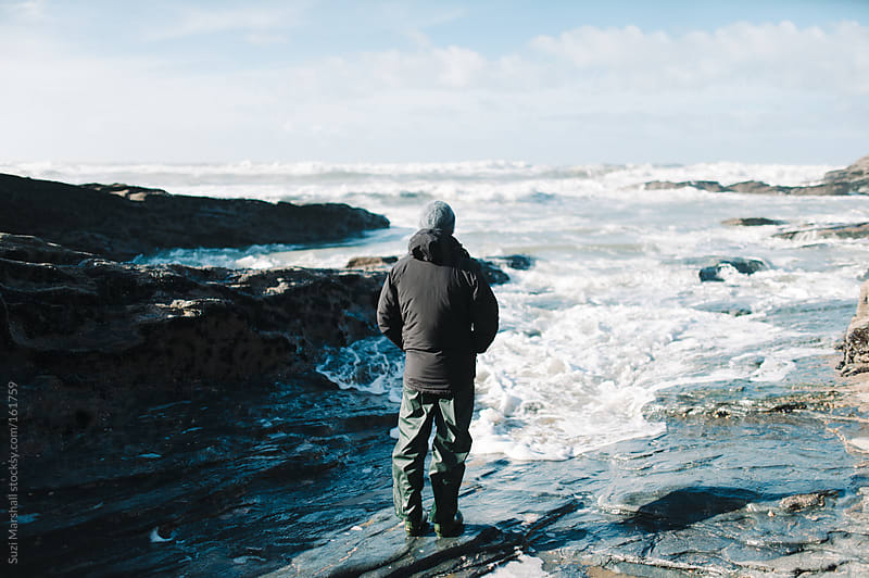 Man standing next to the sea watching the waves by Suzi Marshall for Stocksy United