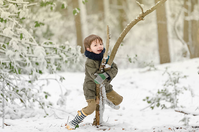 Boy playing in snowy woodland by Rebecca Spencer for Stocksy United
