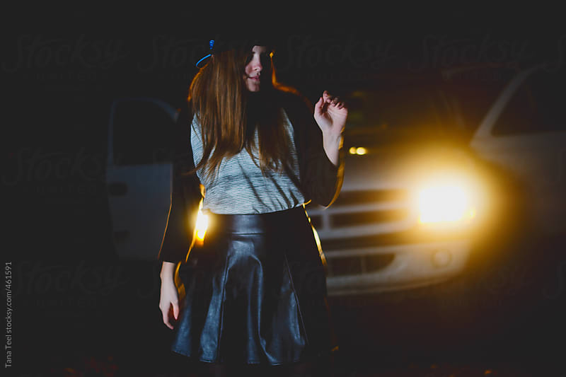 Teenager dancing in front of car lights by Tana Teel for Stocksy United