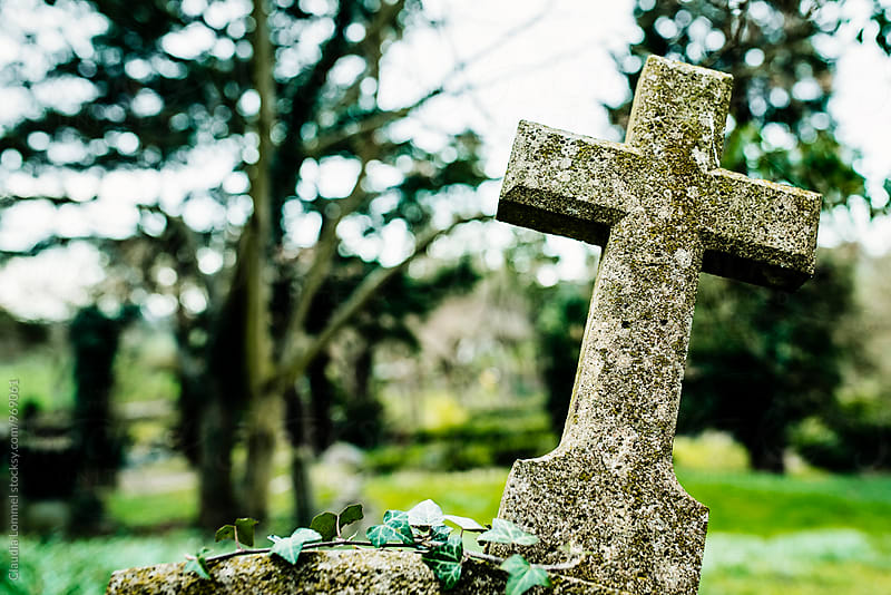 Cross gravestone in a graveyard by Claudia Lommel for Stocksy United