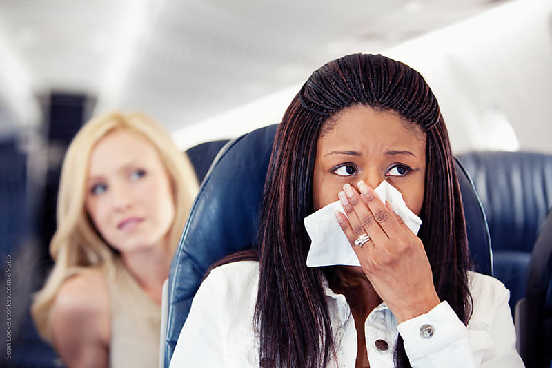 Airplane: Woman Sneezes as Another Is Annoyed Behind by Sean Locke for Stocksy United