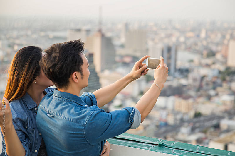Couple taking a photo of a city view together by Jovo Jovanovic for Stocksy United