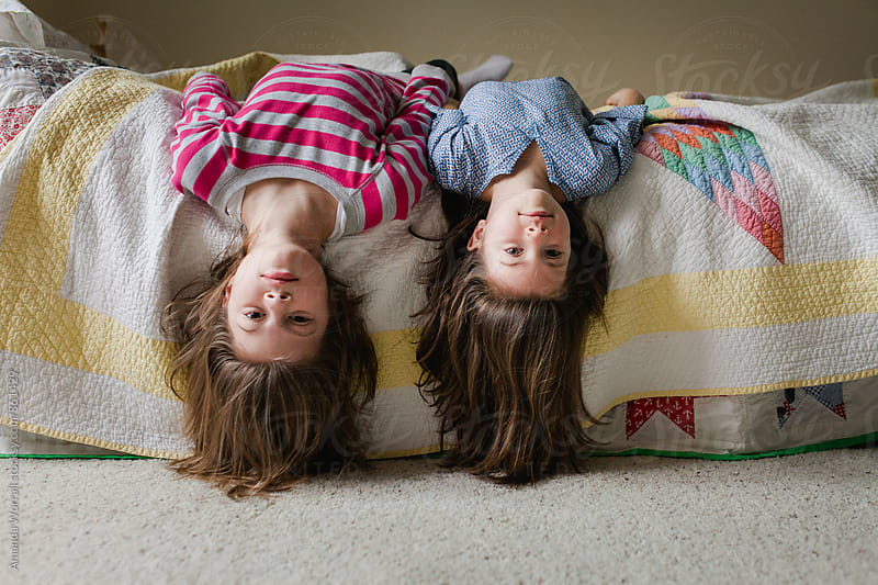 Sisters laying upside down on bed with hair hanging over by Amanda Worrall for Stocksy United