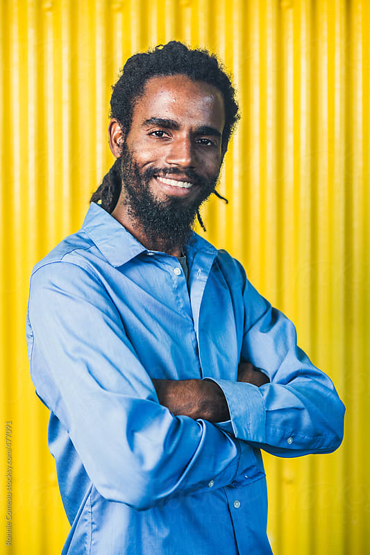 Young Dreadlocked Man On Yellow by Ronnie Comeau for Stocksy United