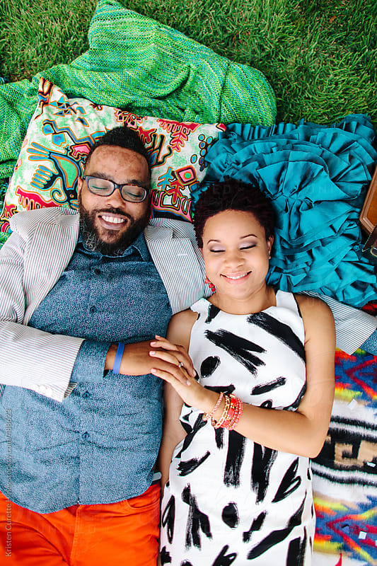 A hipster African American couple laying on blankets in the park by Kristen Curette Hines for Stocksy United