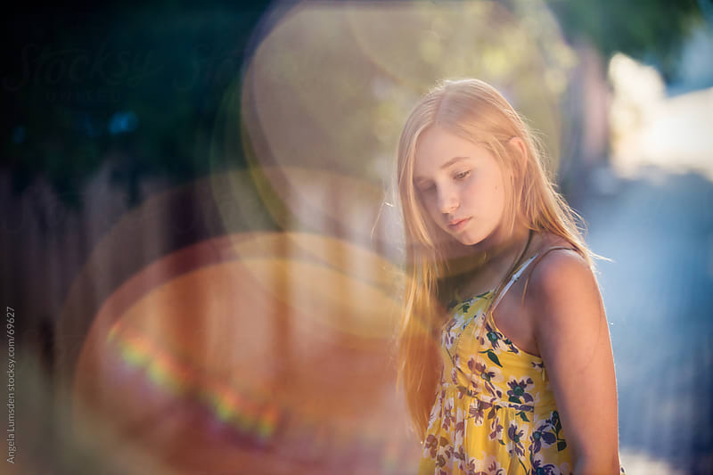 Girl with long blond hair in extreme sun flare by Angela Lumsden for Stocksy United