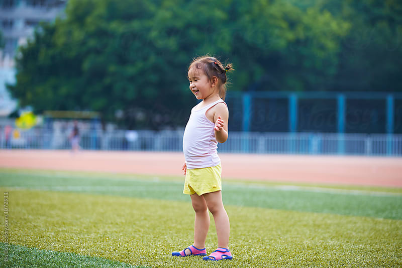little asian or Chinese girl playing football outdoor in the football field by cuiyan Liu for Stocksy United
